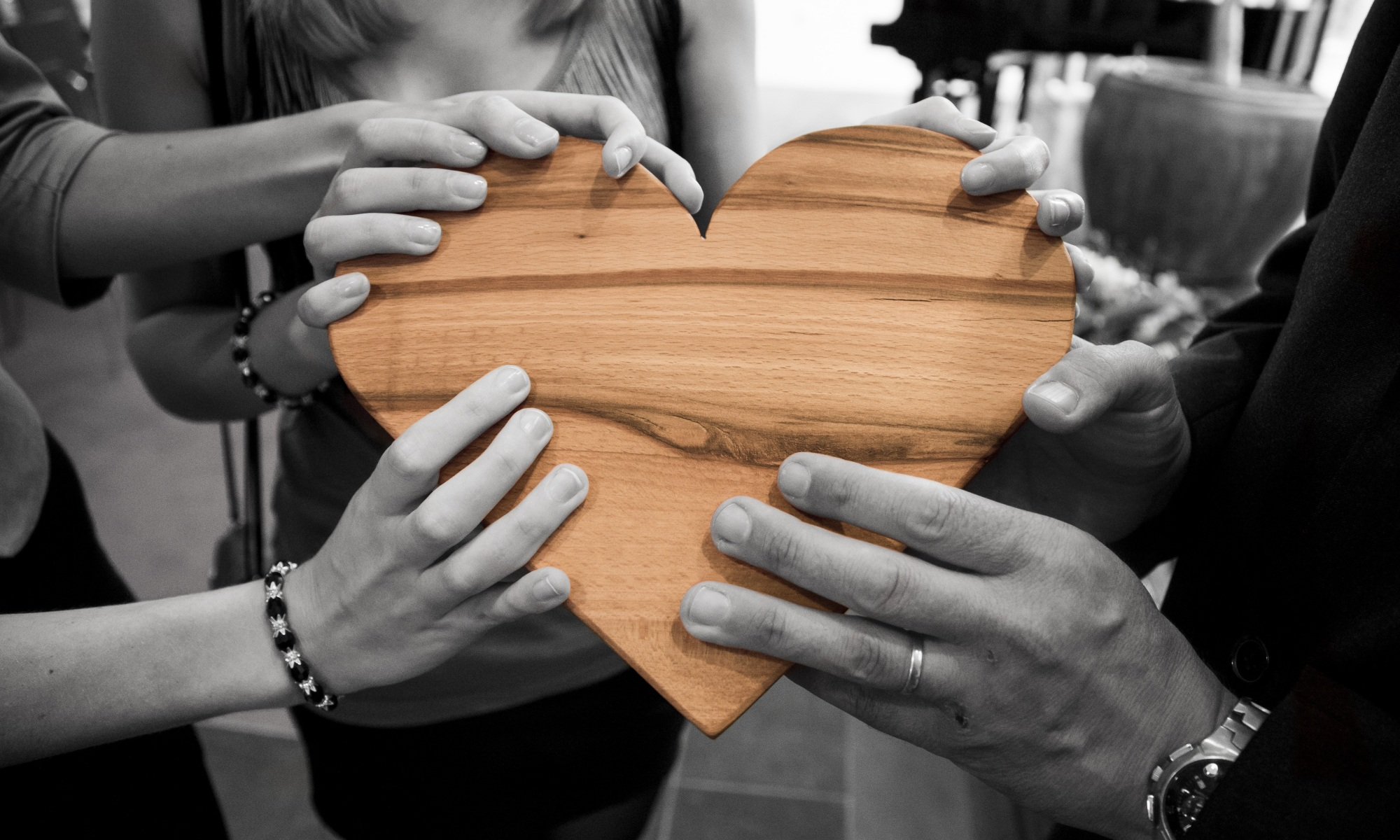 Hands holding onto wooden heart object